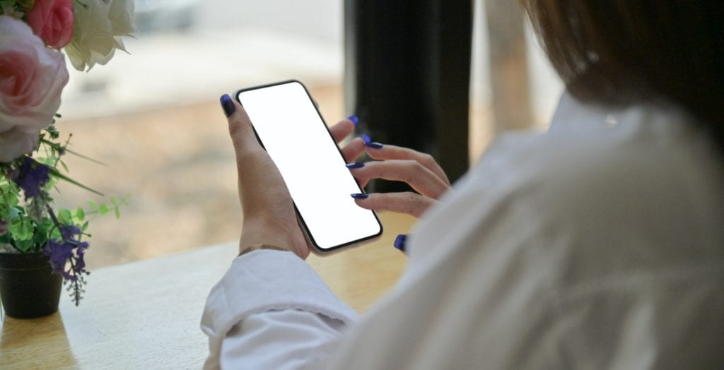 Hand of a young woman using a smartphone to search for information on the internet.