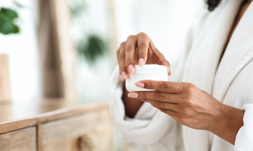 Skin Care Products. Black woman holding jar of moisturizing cream, closeup