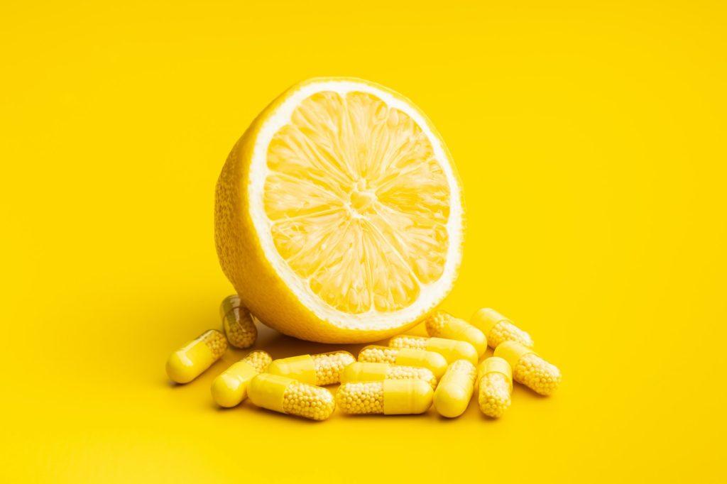 Vitamin capsules. Vitamin C pills and yellow lemon.