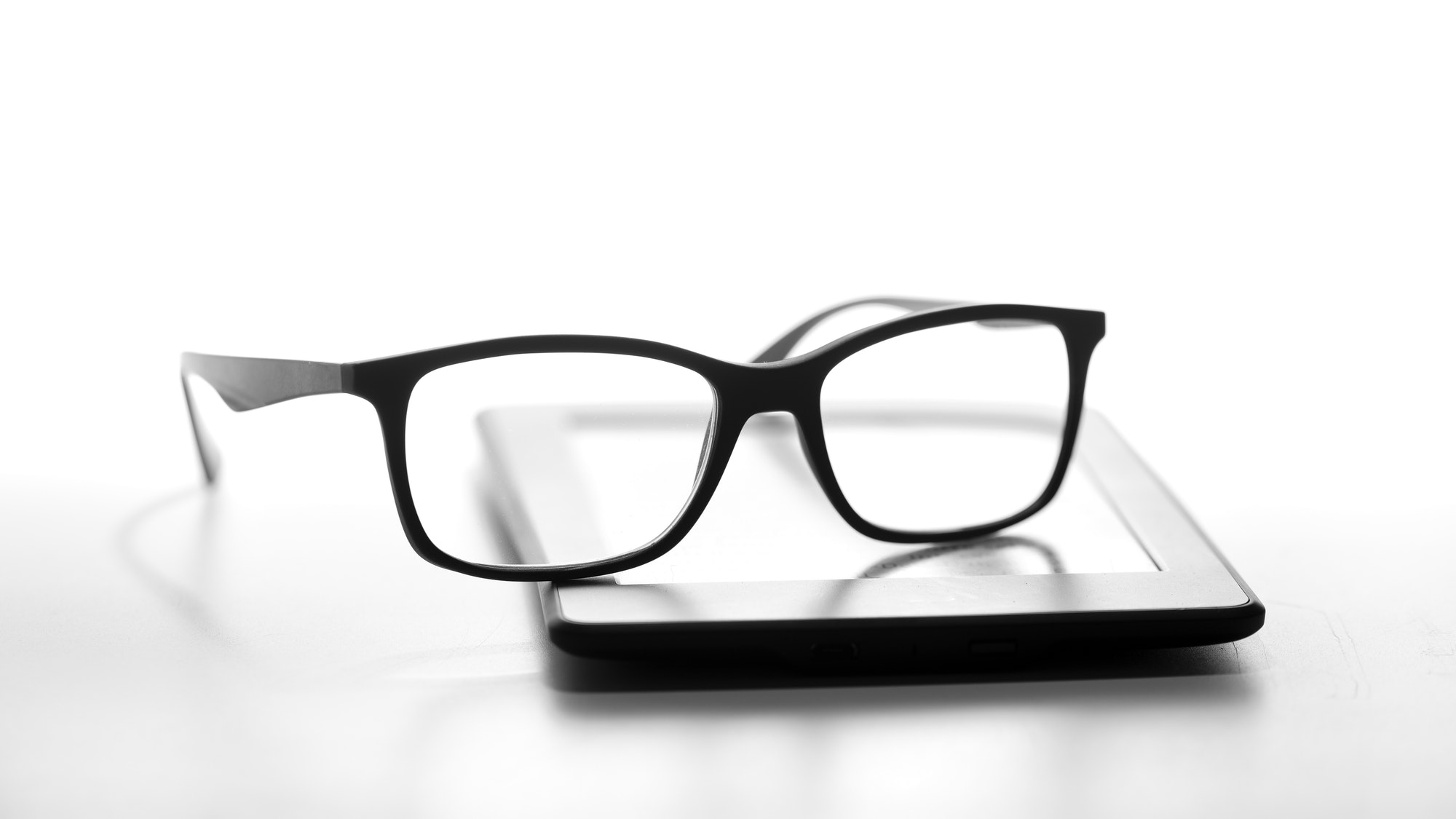 Reading glasses resting on an e-book